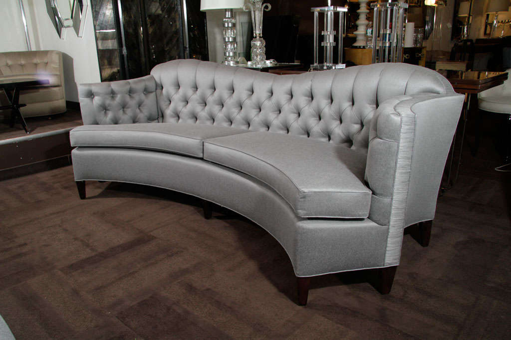 Glamorous 1940s Hollywood curved back sofa with tufted back, scrolled sides and rouched detailing. Newly upholstered in pewter silk/wool with ebonized Mahogany legs.