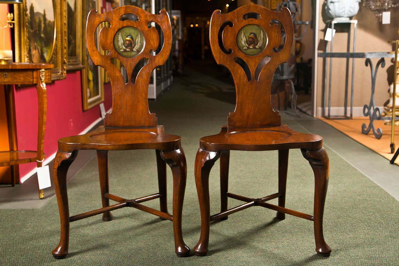 A pair of English George III mahogany hall chairs with later armorial decoration. From the collection of Ann Landers.