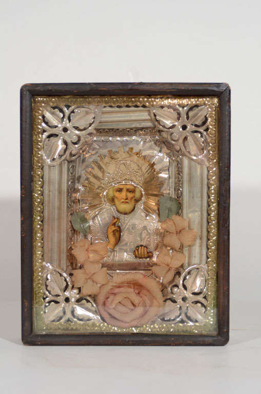 Outstanding antique Russian icon mounted in original wood and glass shadowbox frame. Depicts Saint Nicholas comprised of repousse technique, whereby metalworking is done by hand on the reverse side creating designs in low relief. Features