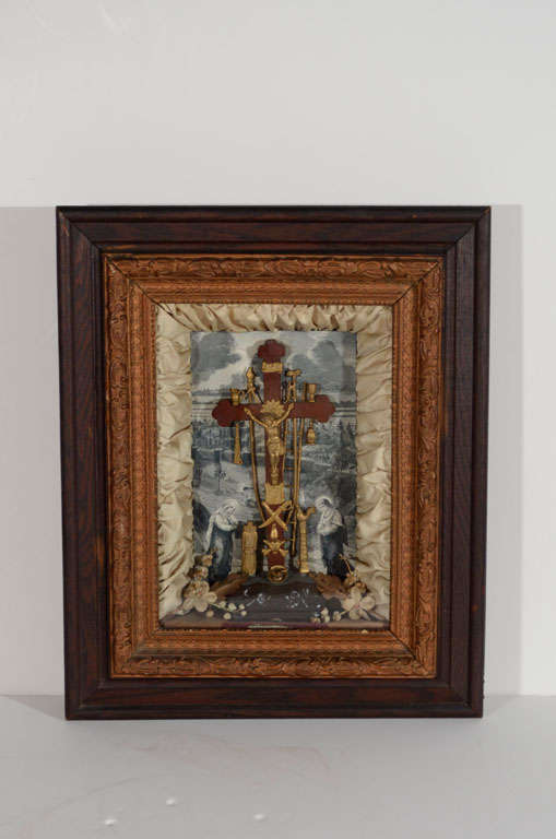 Gilded Age religious shadowbox frame depicting Christ and the instruments of Passion also known as the Arma Christi. Features background print in sepia tones with center wooden cross with a gold Christ as well as various gold metal instruments. The