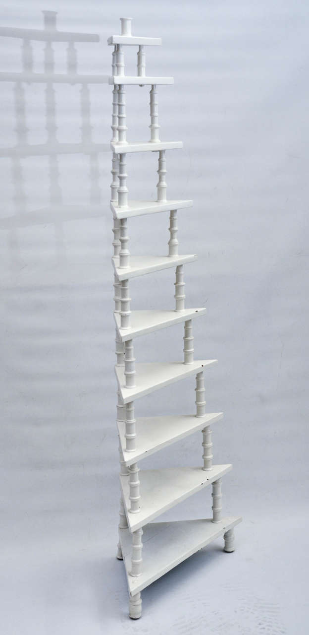 A vintage white painted wood corner shelf with ten levels constructed of thread spools.