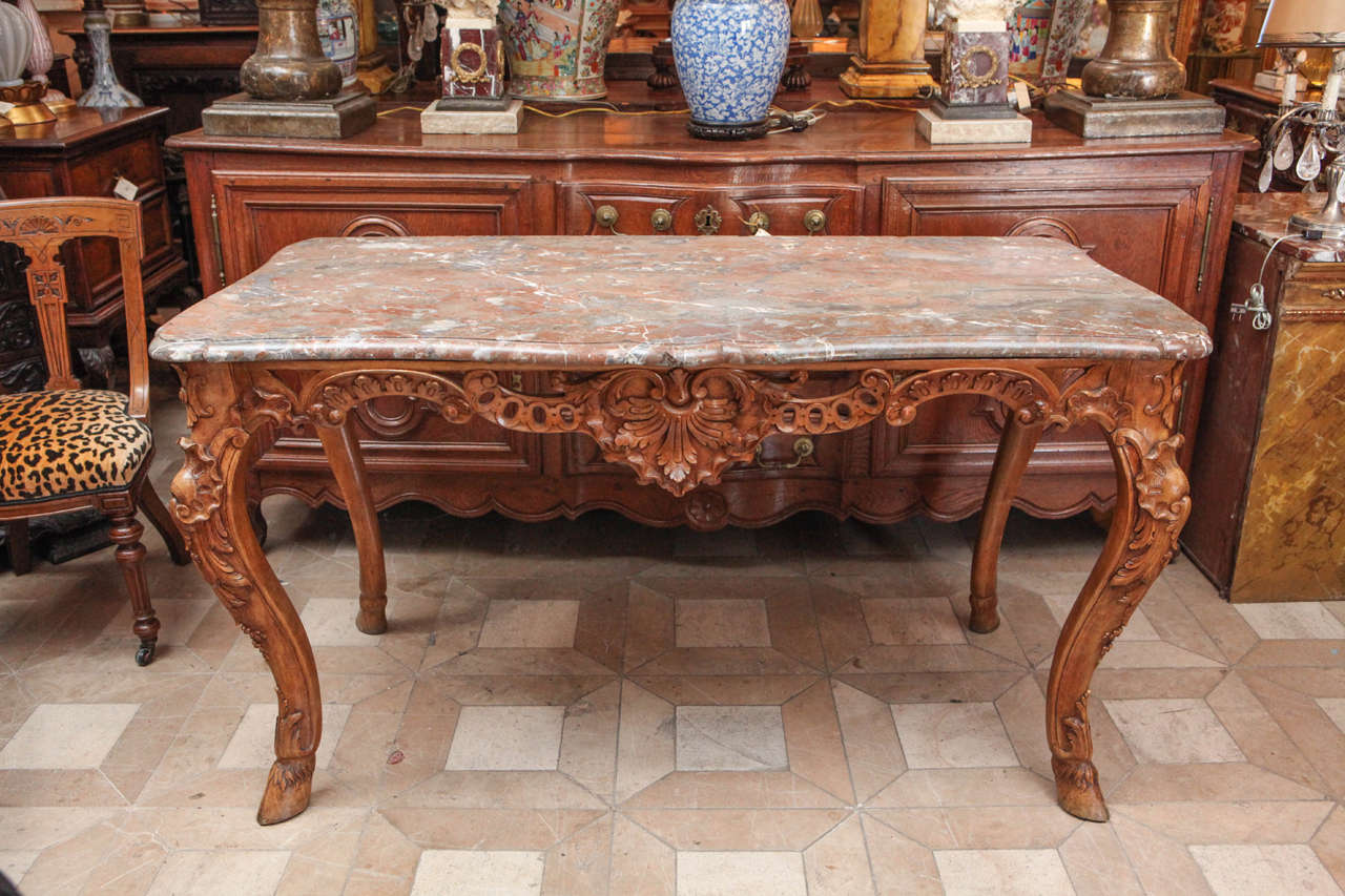 Late 18th century French carved walnut table with original marble top and hoof feet details.