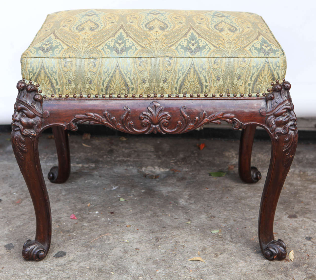 19th c. English carved Mahogany Bench or Stool with Green Silk Paisley Fabric.  The fine carving includes a face motif and scroll feet with nail head detail.