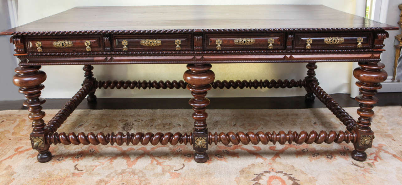 Early 19th century monumental Portuguese solid rosewood writing table or desk with four dovetail constructed working drawers. The finely carved writing table or desk has bun feet with twisted legs and stretcher. It can be floated in the middle of a