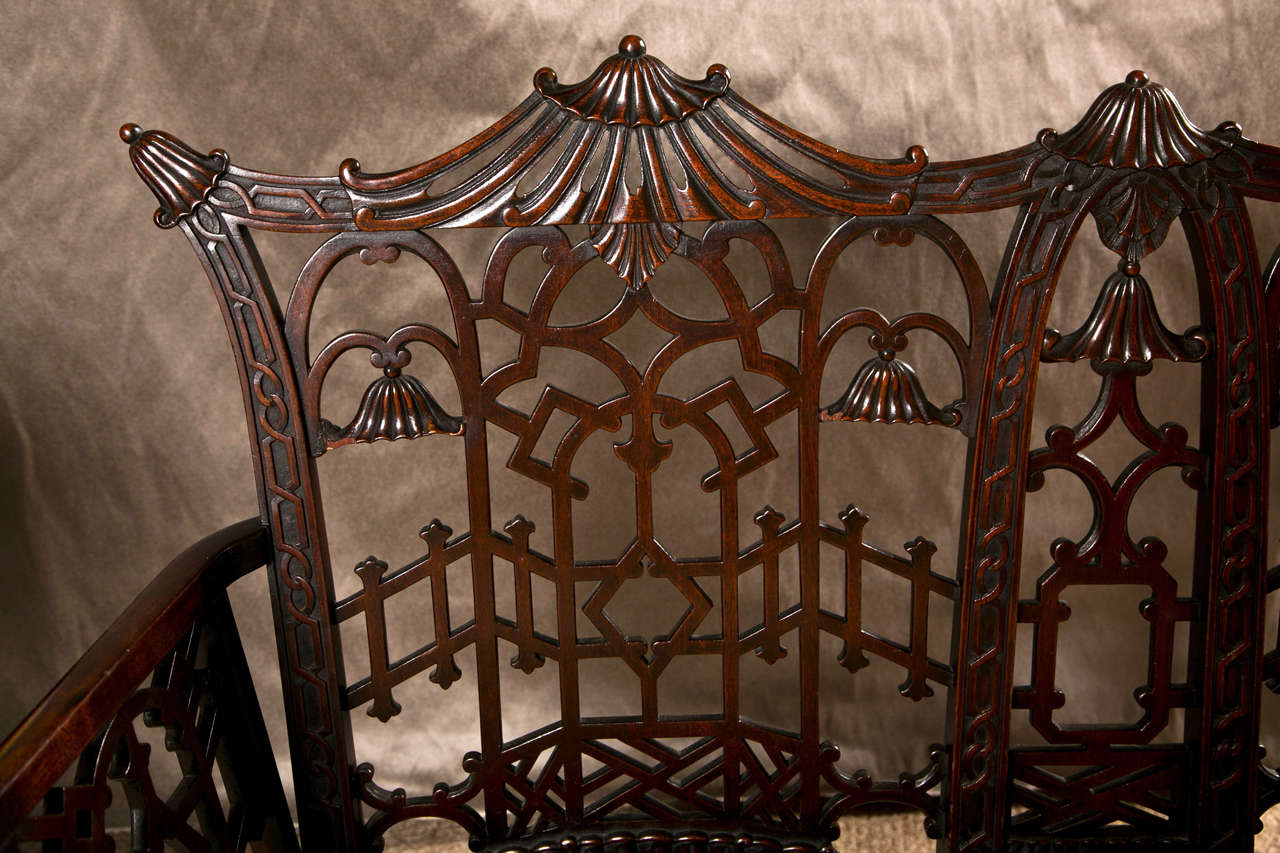 Fine 19th Century Chinese Chippendale Settee with  Upholstered Seat. Fine bamboo carved legs support a carved apron with a custom upholstered seat. Tthe overall back and arm rests with all over carved fret wood design. The top ending in a pagoda