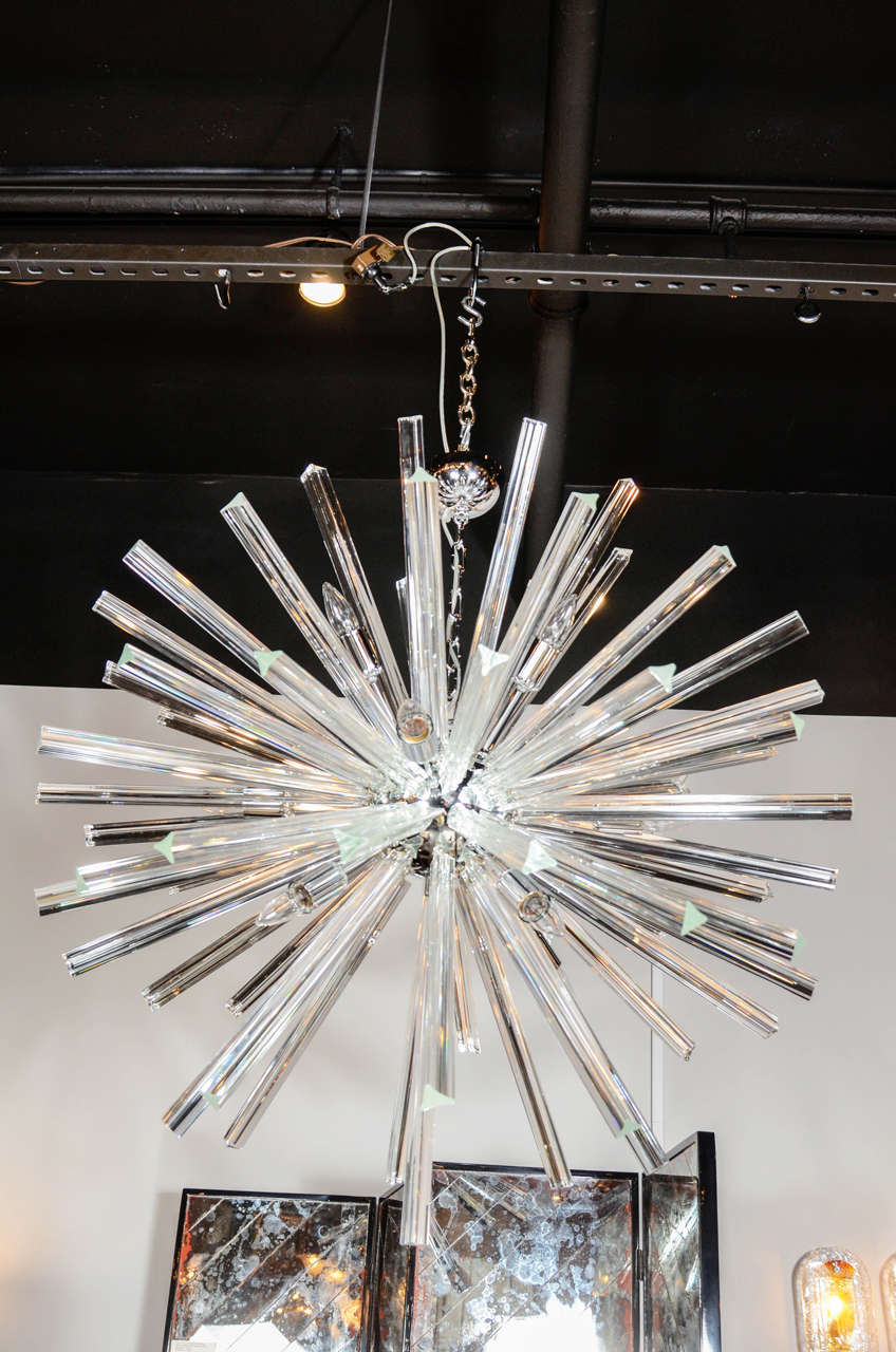 This gorgeous Sputnik chandelier was hand blown in Murano, Italy- the island off the coast of Venice renowned for centuries for its superlative glass production. It consists of a series of Murano Glass Triedre rods emanating from a spherical