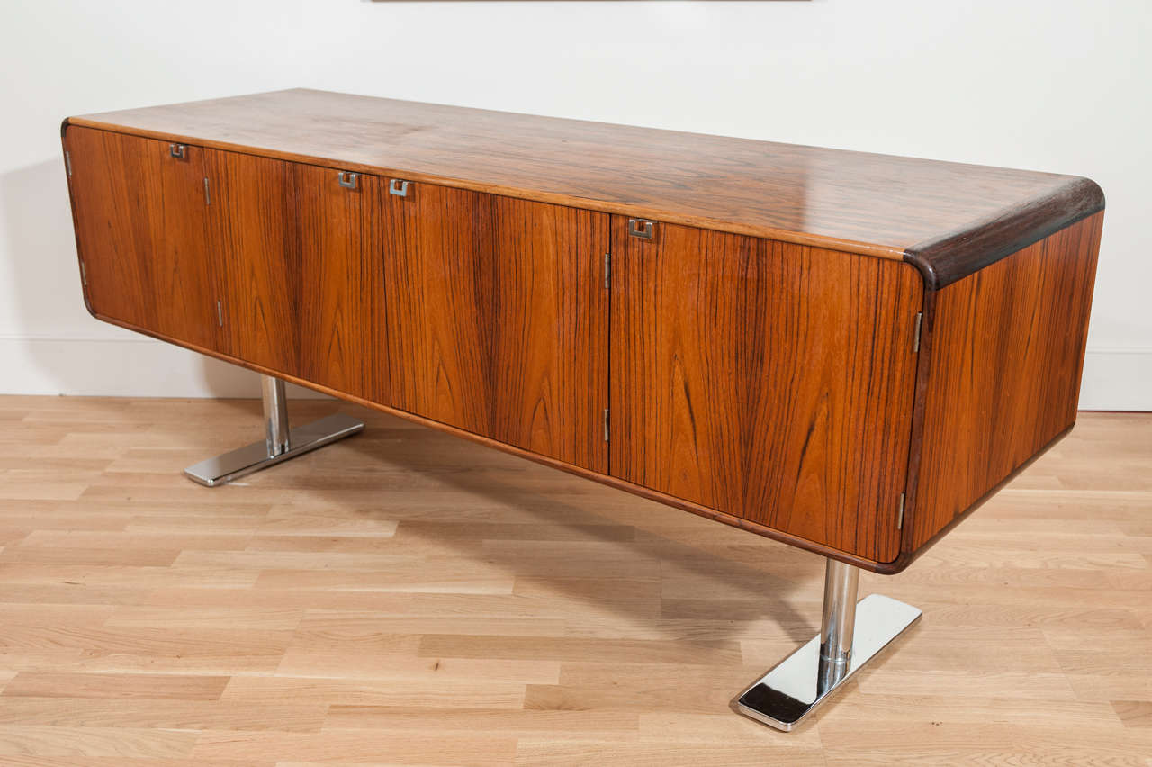 A bench made rosewood credenza with stainless steel base. This classic Leif Jacobsen