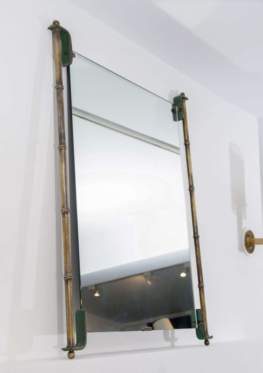 Brass bamboo framed mirror with leather details by Jacques Adnet.