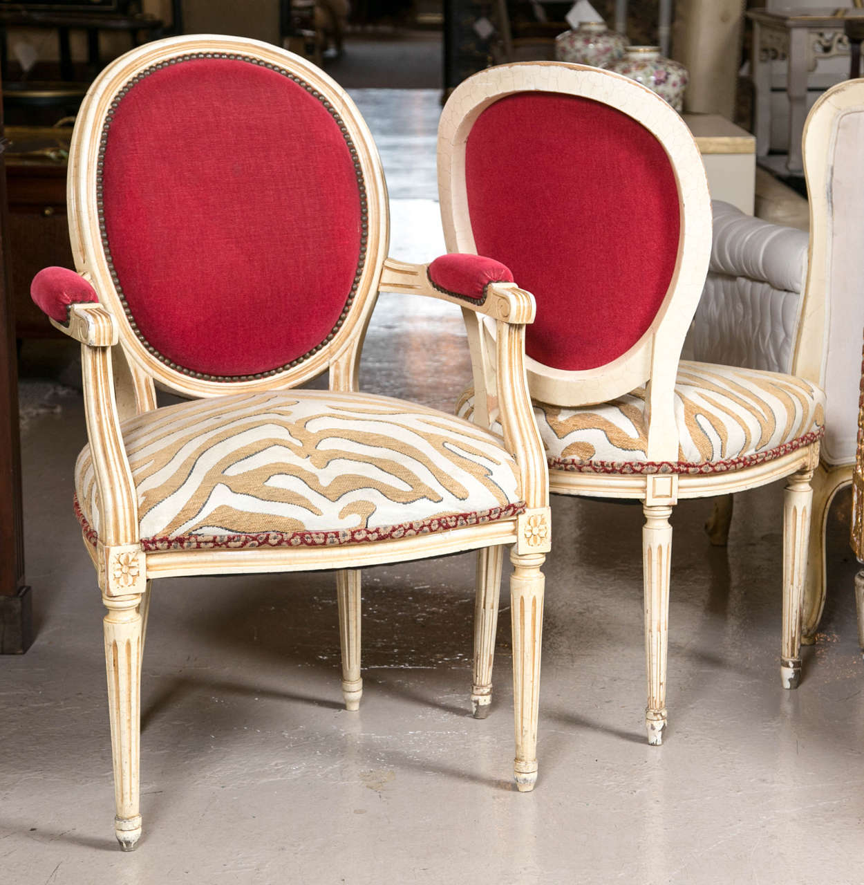 Set of eight Hollywood Regency style French dining chairs. These eight chairs are truly unique accentuating the albino zebra print on the seat and the red upholstery on the top of the back rests and arm rests adds an exciting contract to these Louis