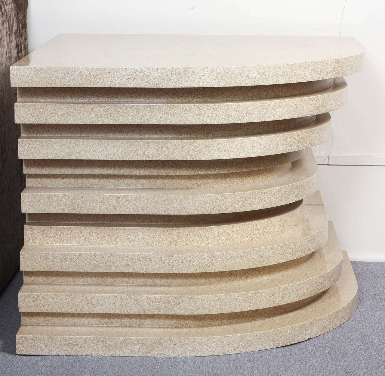Quarter round corner table by Steve Chase.  The table was designed to resemble a stack of different sized elements. It has a warm faux stone finish.