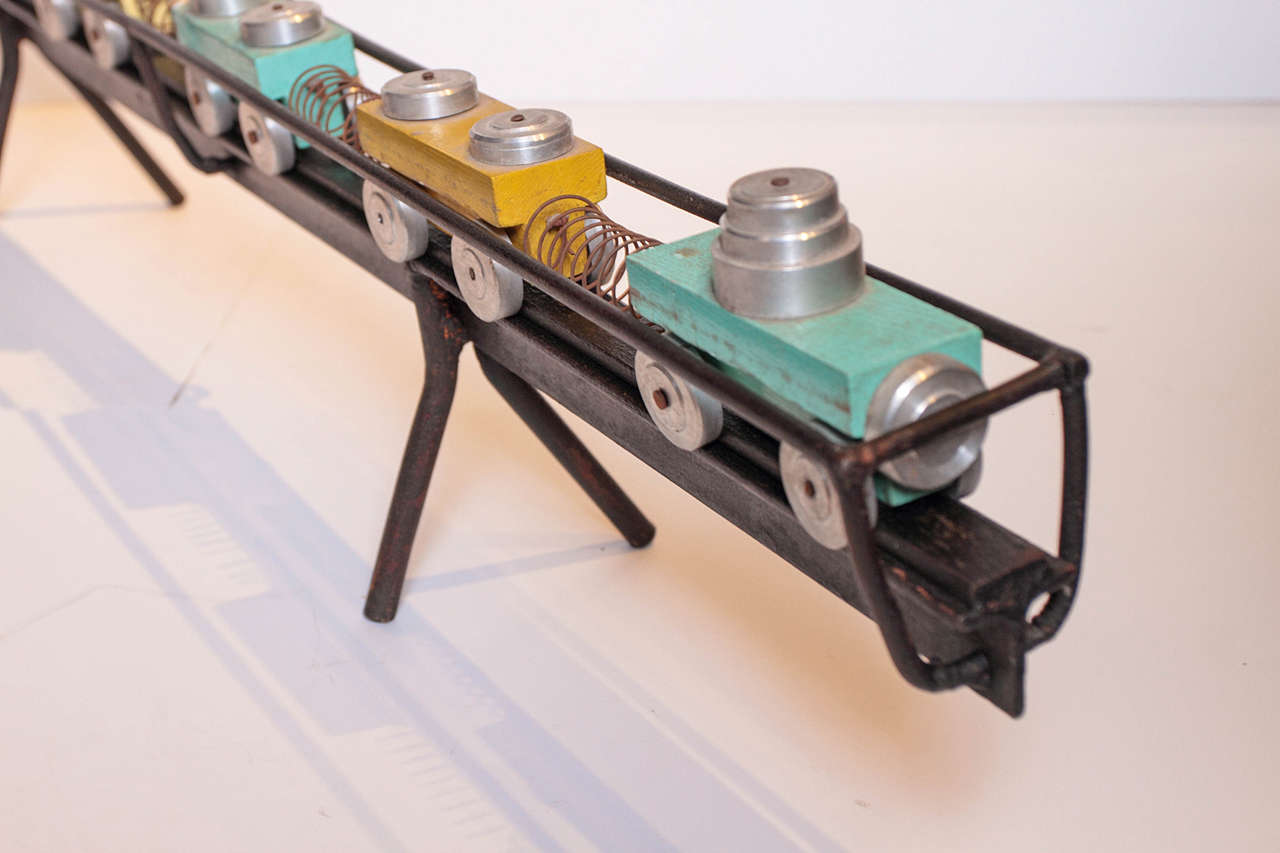 Decorative, hand-painted French train toy set as collectible accessory piece.  Original patina of wooden blocks with characteristic features of chrome metal tops and wheels, and metal springs that connect each cart.   Vintage accessory is placed on