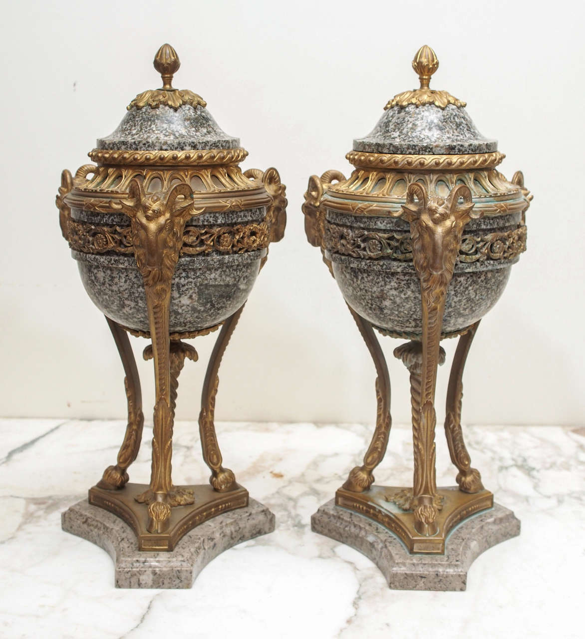 Pair of French Marble and gilt Bronze Cassolet Garniture. In classical form with foliate decoration banding and finial with rams head on trifed monopodial goat hoofs all on a marble plinth.
