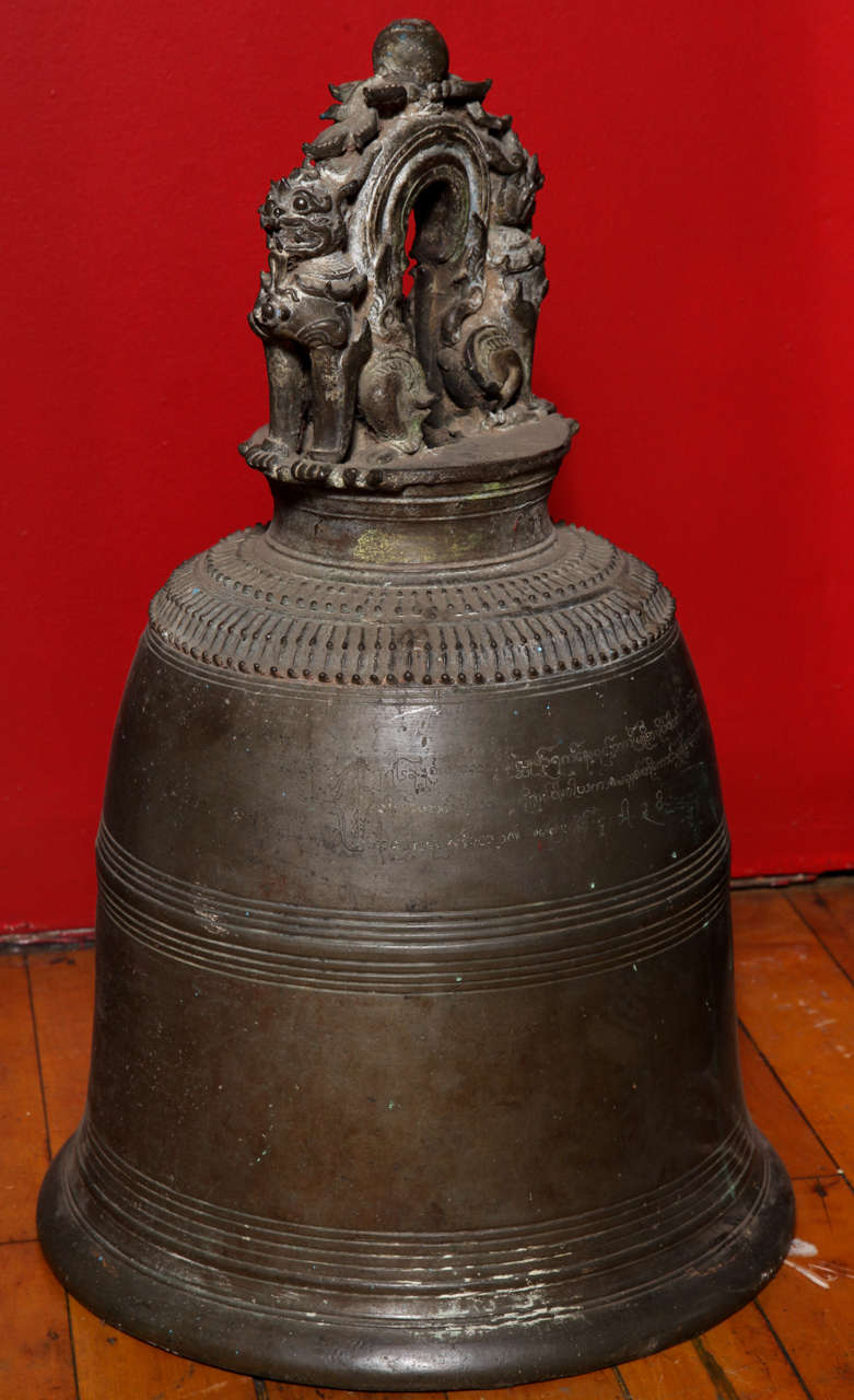 Early 19th century finely cast Burmese bronze temple bell surmounted with two guardian lions. This rare temple bronze bell surmounted with two guardian lions is a great testimony of the Burmese mastery of cast bronze in the 19th century. The bell is