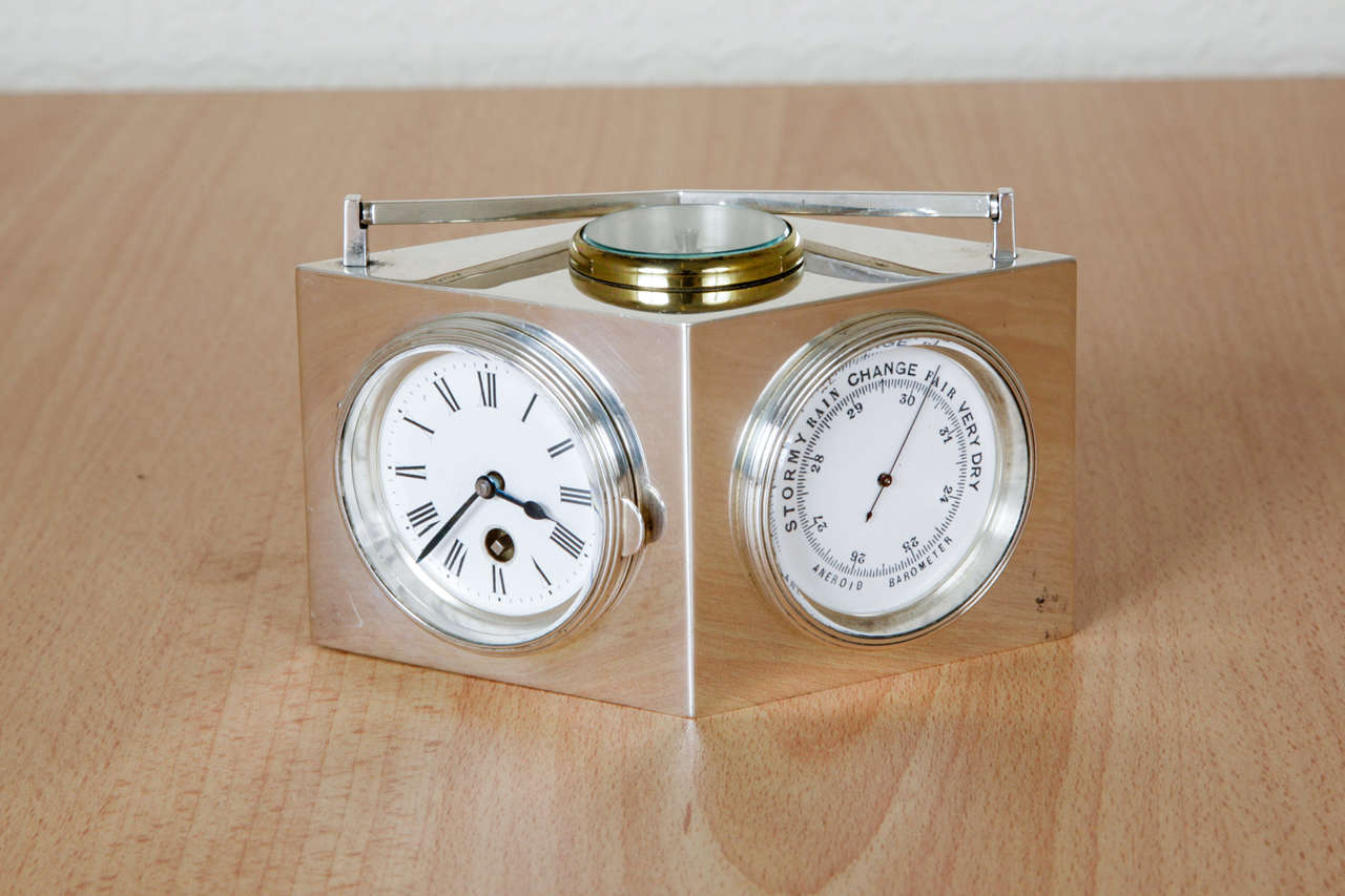 This sterling silver combination clock of lozenge shape with attached handle, was made in France, circa 1910. It has a face to each side, being a clock with a Swiss movement; a barometer; a fahrenheit and a centigrade thermometer; and, unusually, a