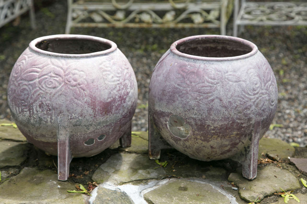 A pair of unique round cast iron jardinieres attributed to Deville & Cie of Charleville, France. The casting has a floral detail. There is drainage below for permanent planting.