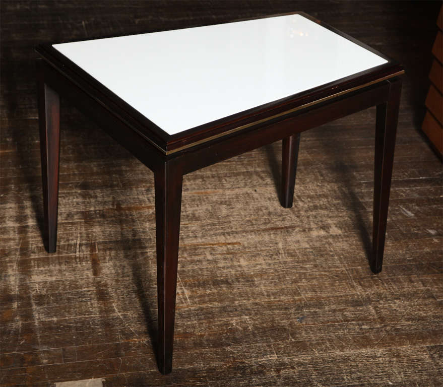 Wedge shaped table of dark stained wood, with brass trim and white Carrera glass insert top. Elegant form with nice detailing.