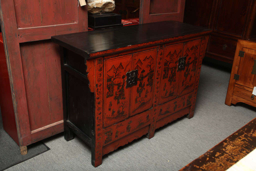 A Chinese red and black lacquered sideboard with gold chinoiserie patterns from the late 19th century. This Chinese 19th Century lacquered wood sideboard showcases typical gold Chinoiserie patterns. The buffet features four doors opening to reveal
