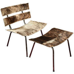 A set of cow hide and chrome chair and ottoman
