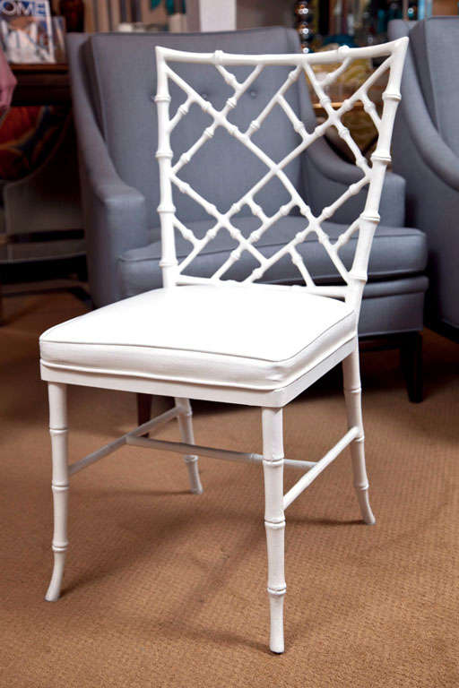 Nice set of white painted faux bamboo metal chairs. Chinese Chippendale style fretwork backs and new ivory faux ostrich upholstery.