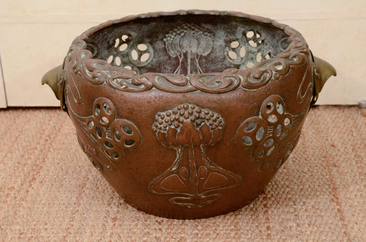 This rare German Art Nouveau, or Jugendstil, planter has a hand-hammered copper body executed in the Japanisme taste with low relief stylized lotus flowers, undulating wave forms with pierced circles throughout, a raised wave form rim, and flanking