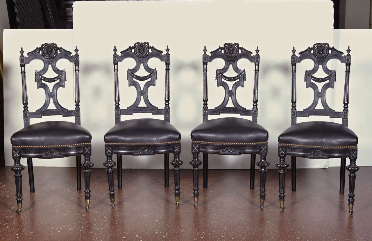 Set of four 19th c. ebonized side chairs, ornately carved with ribbon and garland motif, masks and finials.  Turned front legs with castors.  Upholstered in black leather with nail-head trim.  Circa 1860.