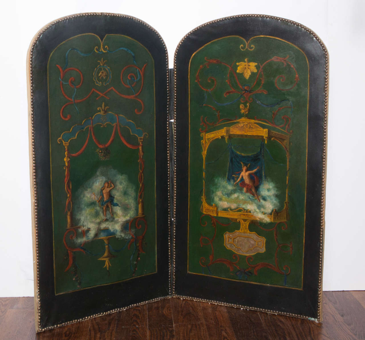 Two panel folding screen with oil paintings depicting mythological male figures.  Back of screen is upholstered in silk damask.  Brass nailhead trim.  Fabric hinges.