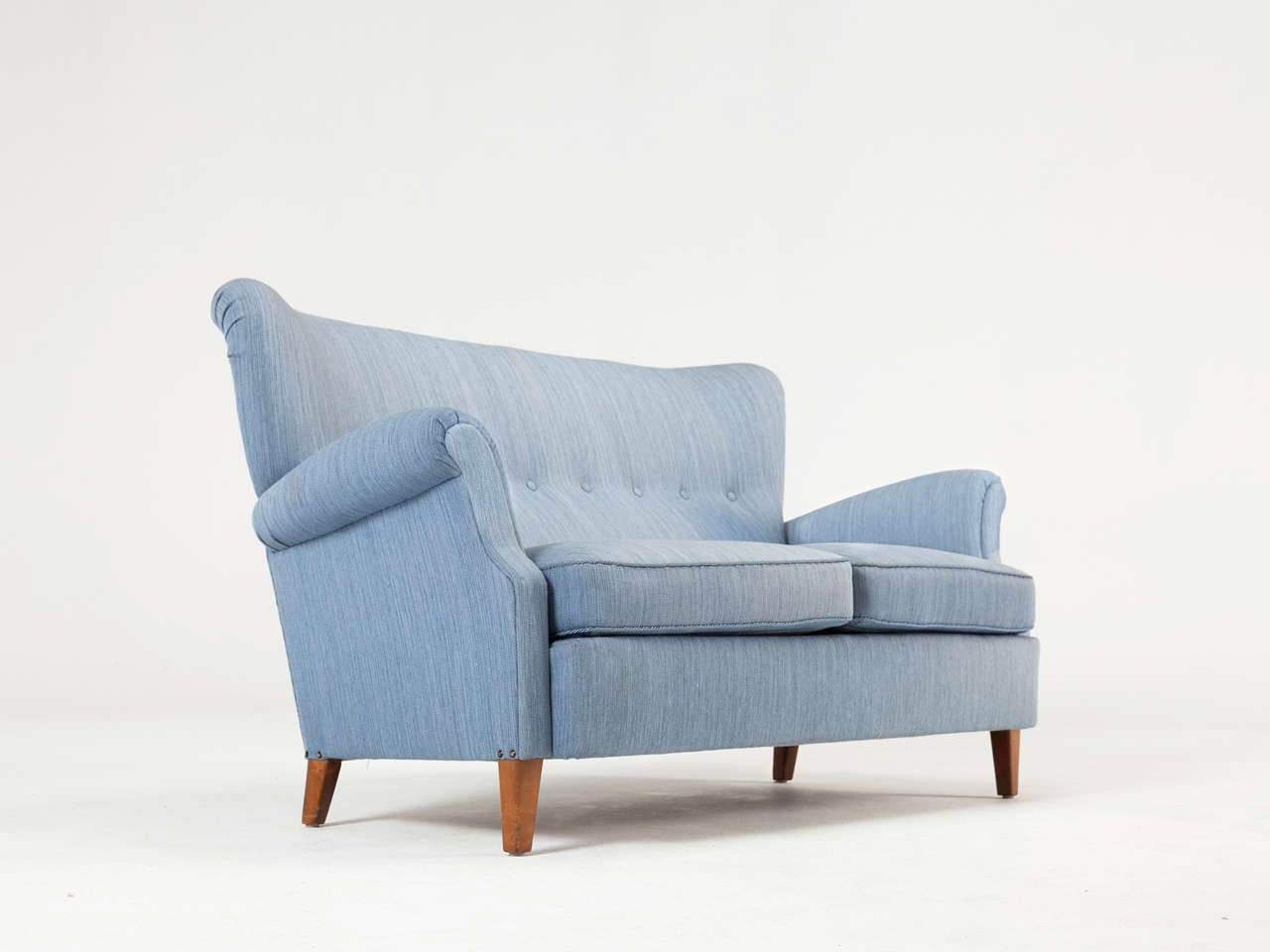 Scandinavian two-seater sofa upholstered in original blue wool fabric.  Designed in the style of Carl Malmsten.  The back has deep-stitched buttons and the seat consists of two loose cushions. The armrests are elegantly shaped. The legs are made