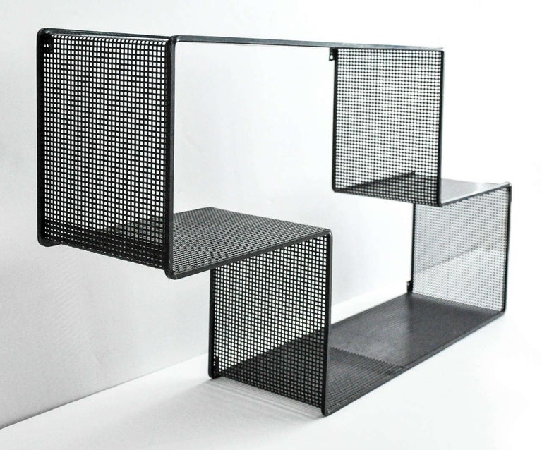 An enameled metal shelf by the distinguished French designer Mathieu Matégot (1910-2001). Mategot pioneered the use of perforated sheet metal and lacquered steel in his furniture and decorative objects. Original condition. An elegant and iconic