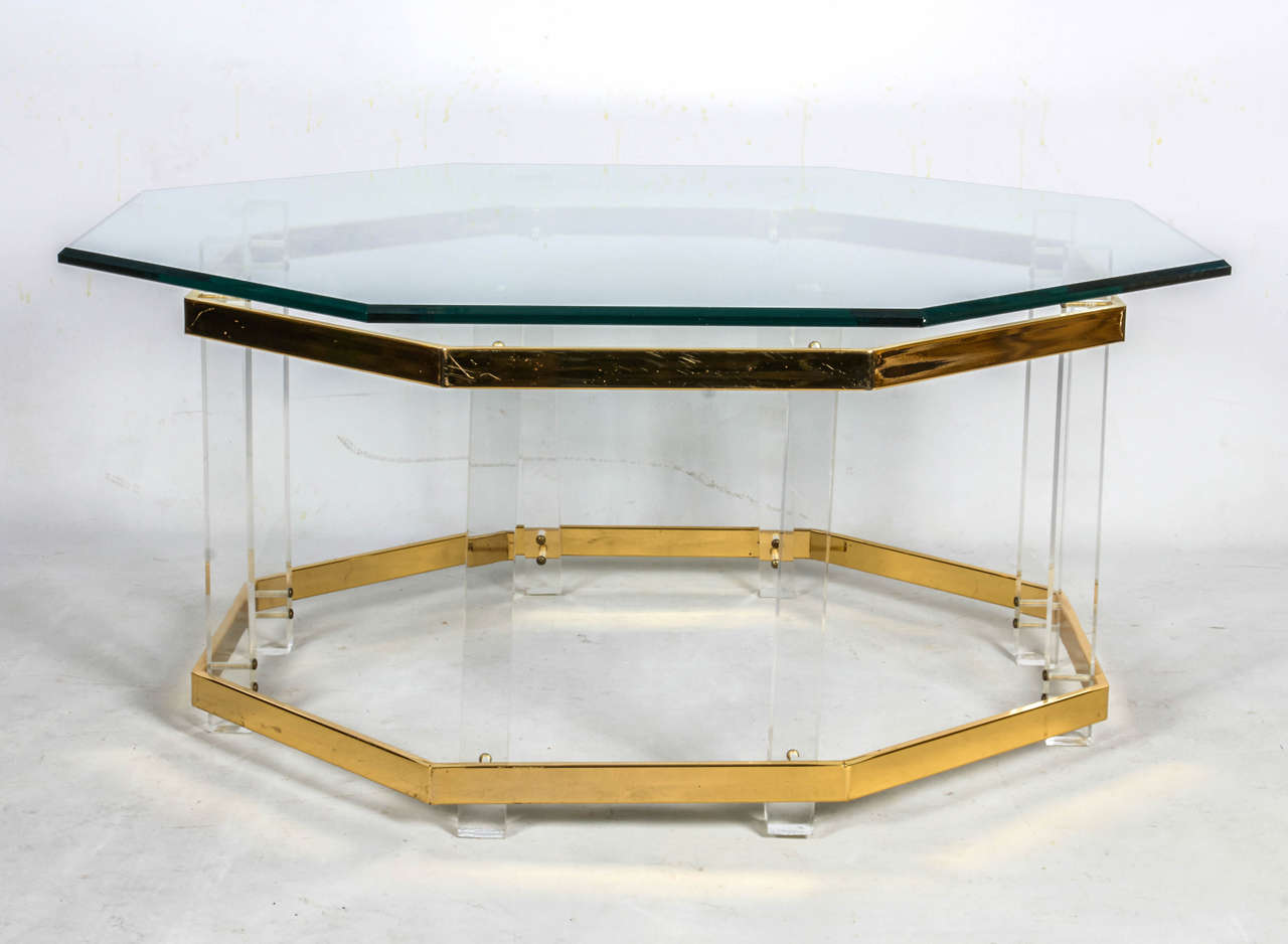 Octagonal coffee table with a beveled glass top over Lucite supports and brass trim. The glass top aligns with the octagonal base below. Please contact for location.