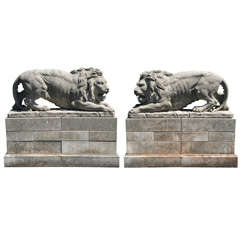 A lareg pair of French sculpted limestone models of lions on plinths