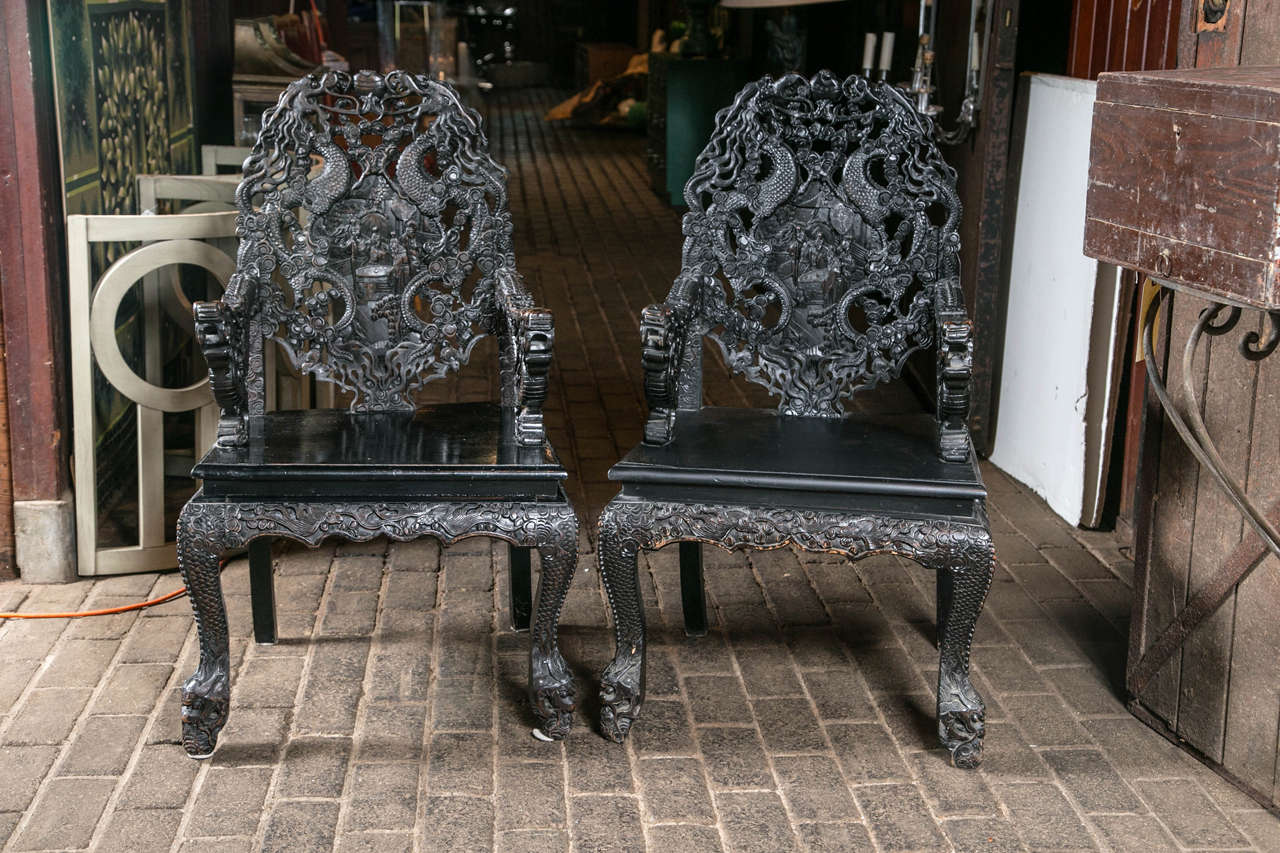 Exotic and dramatic, intricately carved pair of Asian armchairs from the 1920s.
