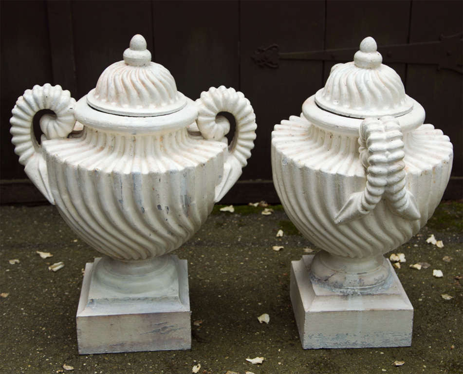A unique pair of cast iron swirl design urns with original lids