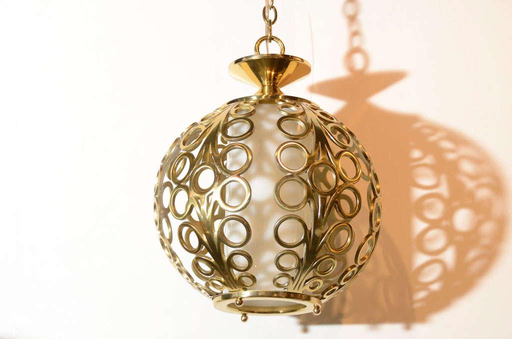 brass globe ceiling pendant with stylized filigree design
