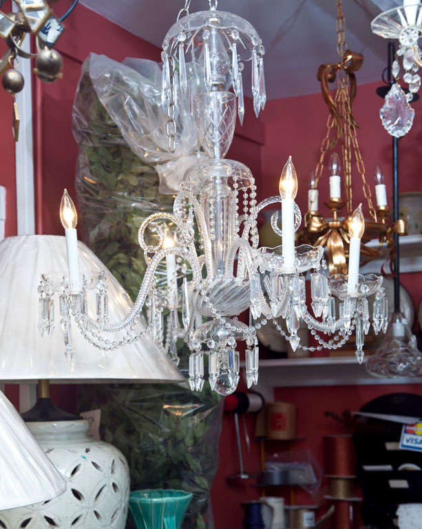 A glittering four-arm chandelier, all of Venetian glass and dripping with cut crystal.