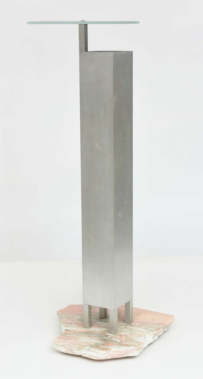 "The glass canopy ""floating"" above a stainless steel square column with light source, on legs, on a marble rough cut stand."