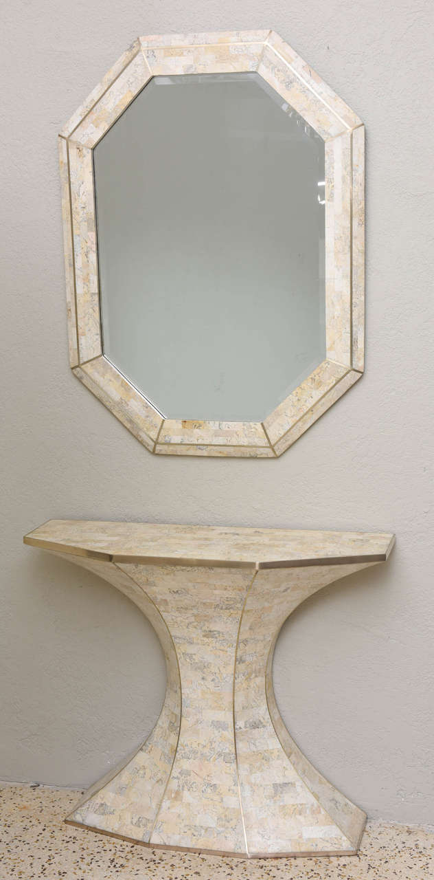 Tessellated marble mirror and console by Maitland-Smith. We love the Brasilia-inspired shape of the console and the gleaming brass inlays and trim. A rich and decadent visual moment! Mirror measures 40.5in. H x 30.5in. W x 1.25in. D. (Console