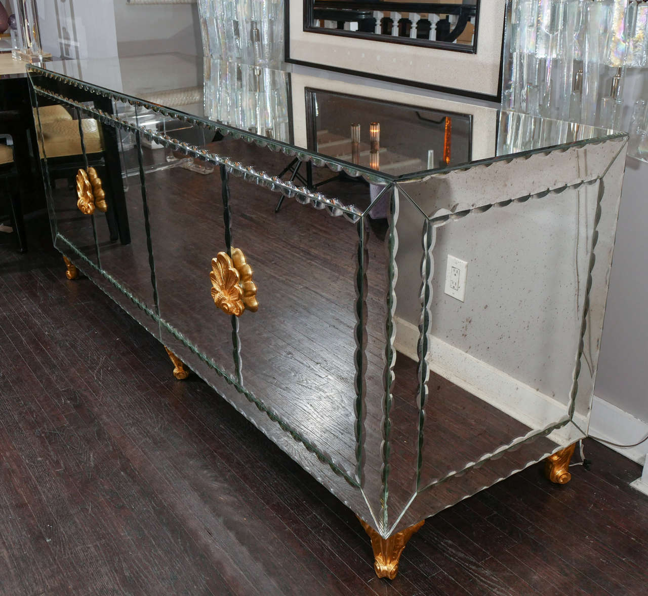 Mirrored buffet with pie crust beveled edges and gold leaf hardware.