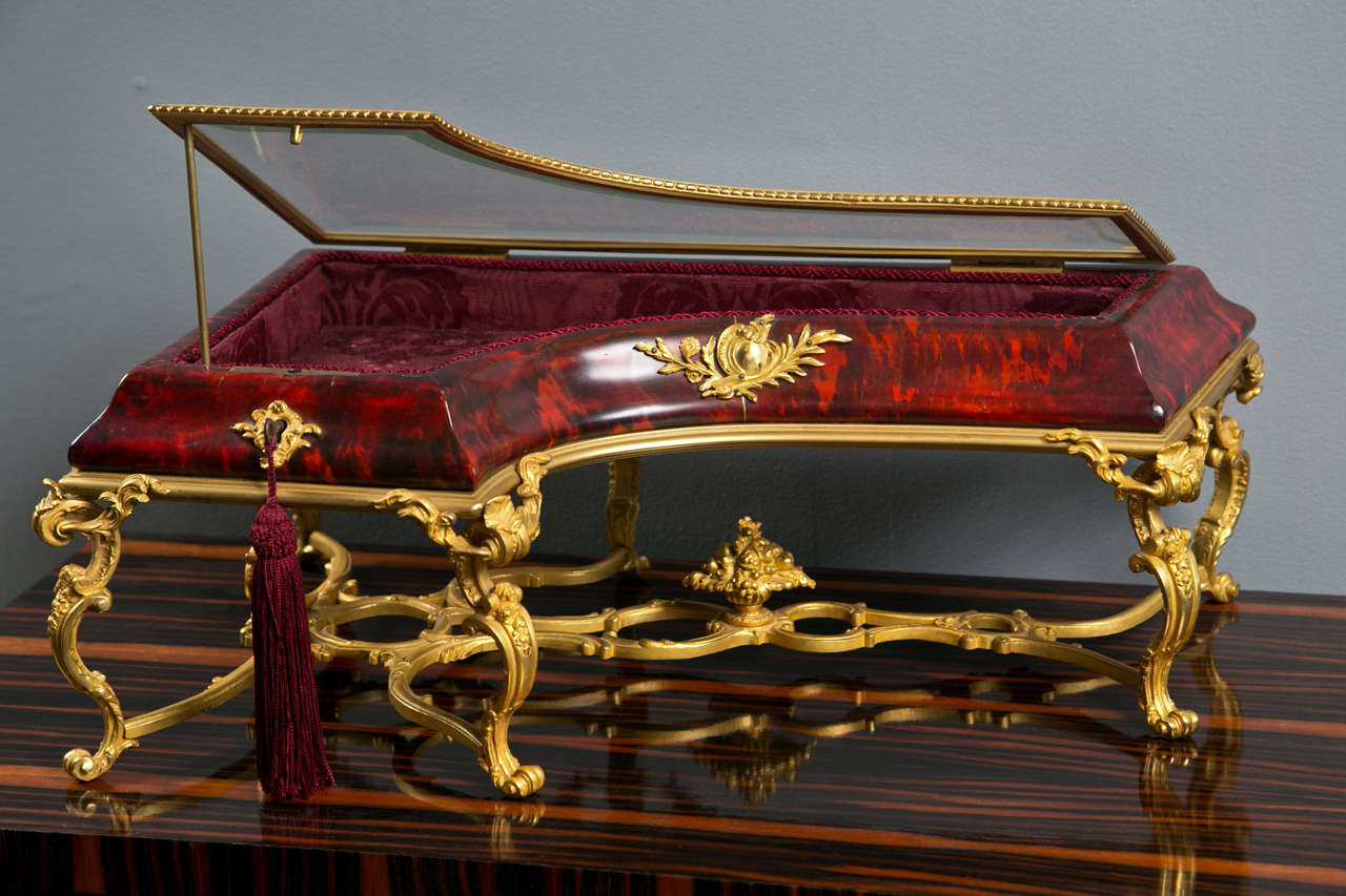 A 19th century French red tortoise shell table top vitrine in the shape of a piano with gilt bronze mounts.