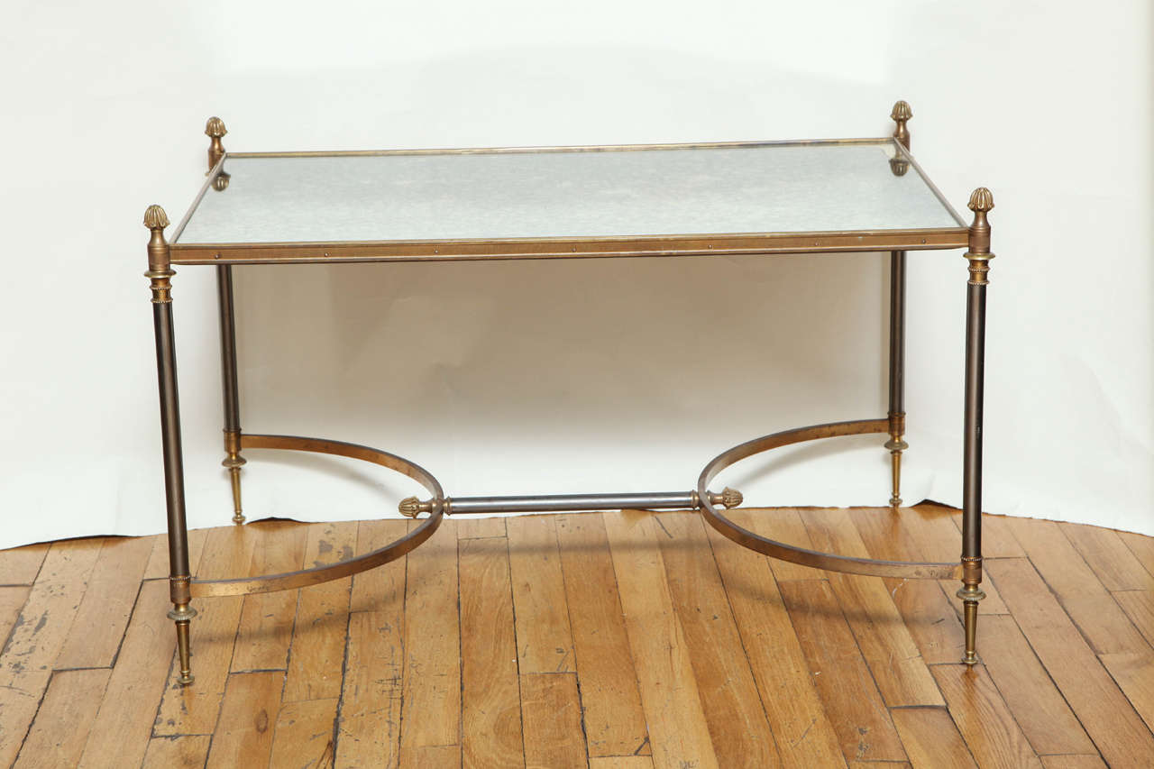 A French Louis XVI style coffee table with antique smokey mirror top having gilt bronze edge supported by steel legs having gilt bronze finials and turnings. The legs supported on the lower section by two c-shaped elements in gilt bronze joined by