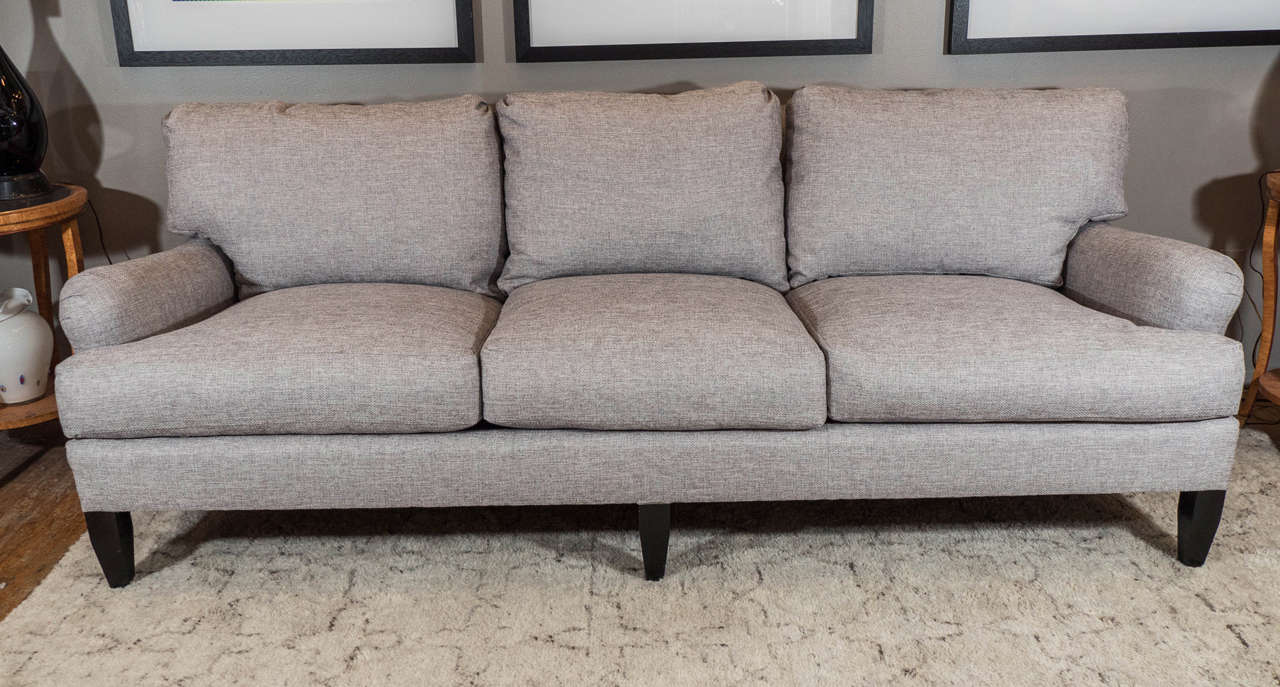 A vintage circa 1980s three-seat, English arm sofa, newly reupholstered in grey linen with down cushions, on tapering, ebonized wood legs. Excellent vintage condition, with minimal wear, consistent with age and use.