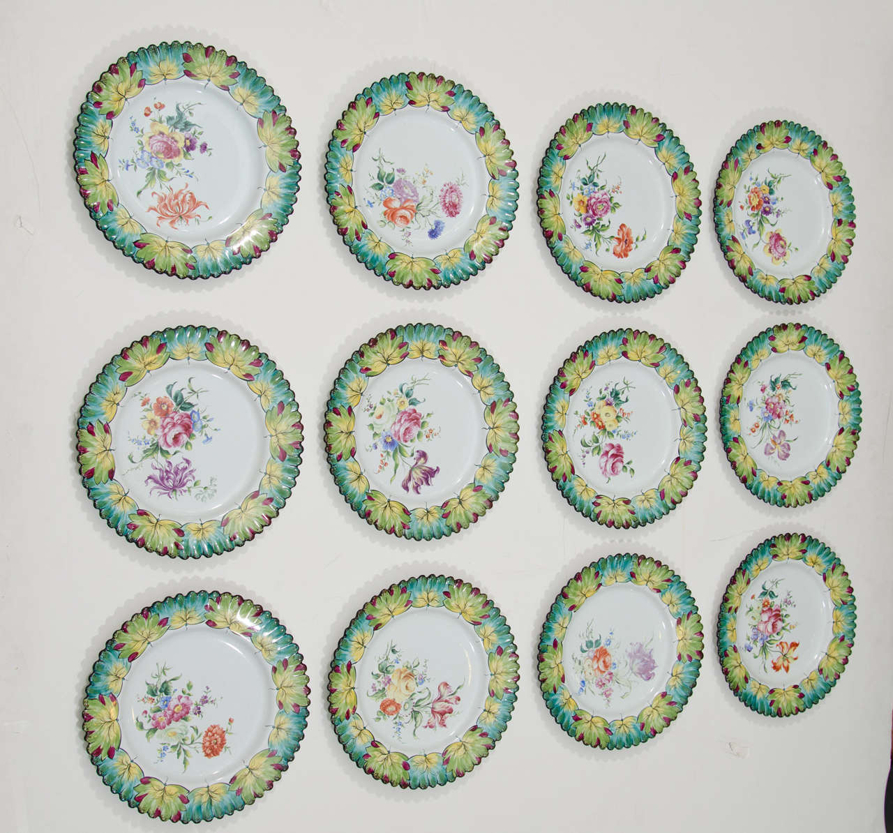 A vintage set of twelve rare hand-painted plates with scalloped edges by Camille Le Tallec for Tiffany & Co. Manufactured in 1964, and painted by an Artisan with initials G.M.  Ten plates are in perfect condition.  One plate has a tiny flea bite