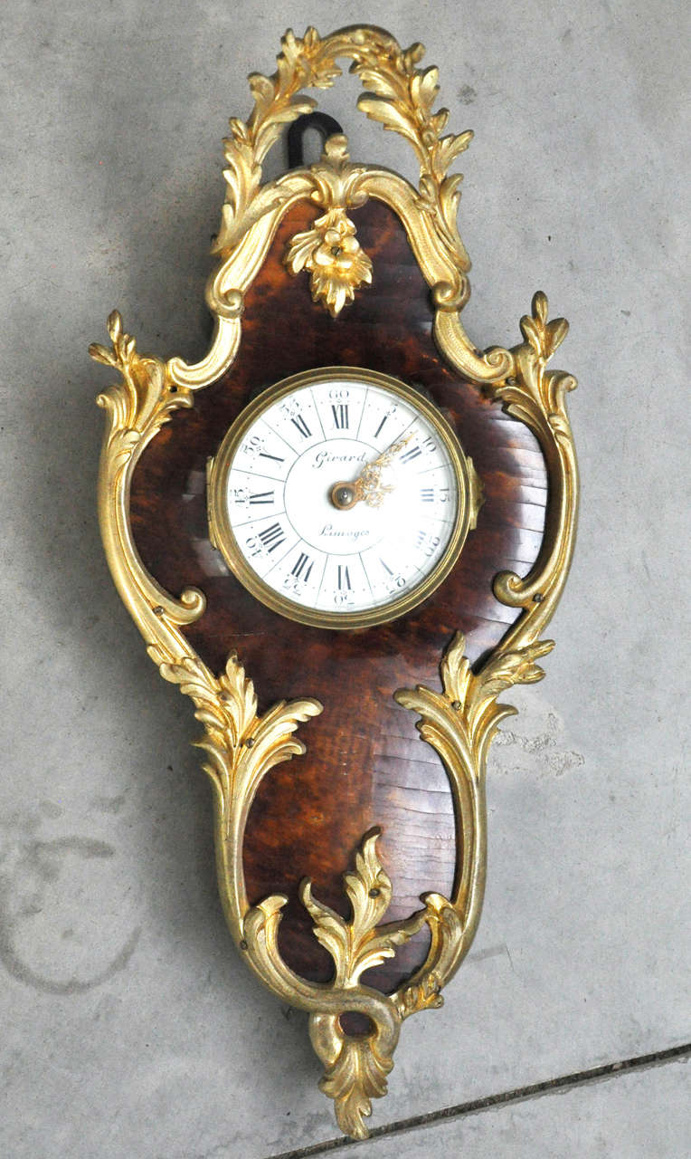 A petite cartouche shaped Cartel clock in the Louis XV style with tortoiseshell body framed with gilt bronze leafy ornamentation. Hinged convex glass door reveals white enameled dial with black Roman and Arabic numerals, pierced gilt hands, signed