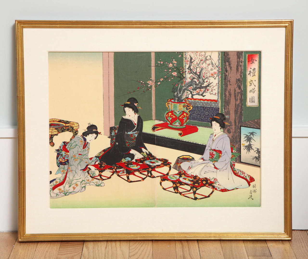 This Meiji-period color woodblock by Toyohara Chikanobu (1838-1912) depicts three elegant female courtiers in traditional dress taking refreshments. This diptych, from the issued triptych, has been mounted in a silk-wrapped mat fitted in a giltwood