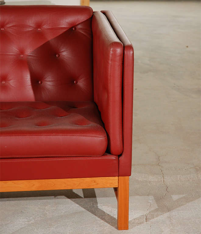 Red leather sofa with tufted seat and back, and a wood base.