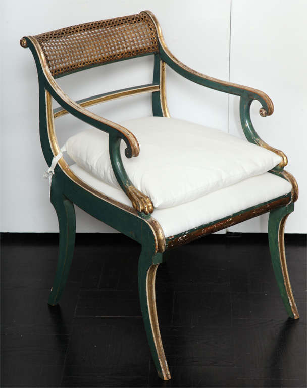 19th Century green painted  & giltwood open arm chair, cantered cane back railing, downswept arms on scrolled supports, saber legs