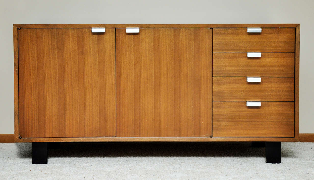 A circa 1950s George Nelson Designed Credenza for Herman Miller.  Walnut wood, ebonized wood legs and nickel drawer pulls.