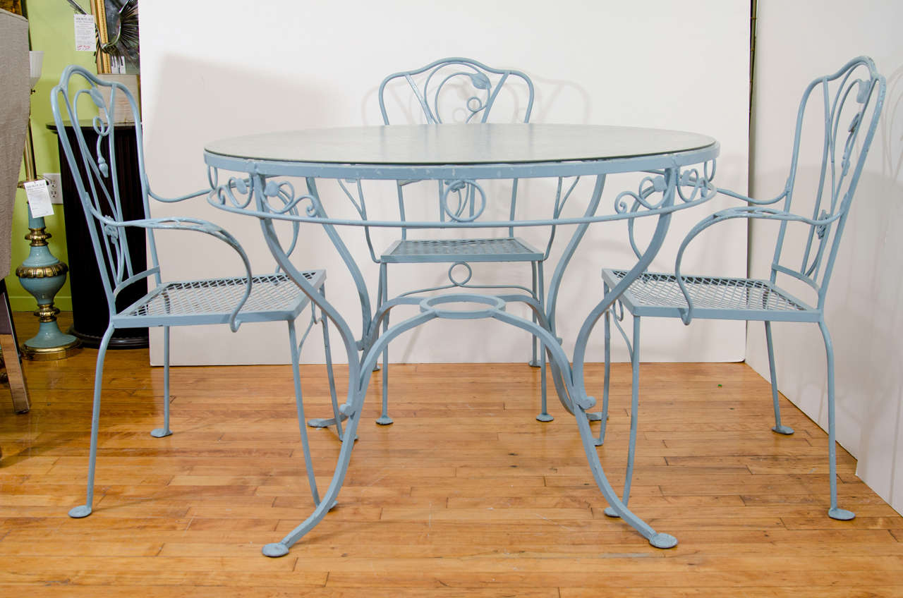 A vintage patio or garden set comprised of a wrought iron table and chairs by Salterini. The table has a tempered glass top and the four chairs and the table are painted light blue and decorated with a floral motif. Signed Salterini on the inside of