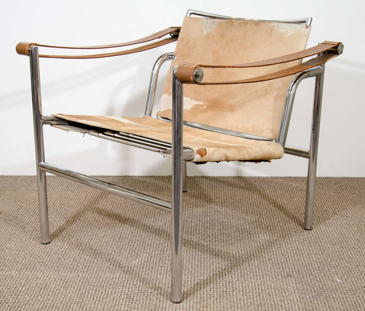 A Vintage LC1 Sling Chair In Cowhide With Adjustable Back, Leather Armrests  And A Tubular