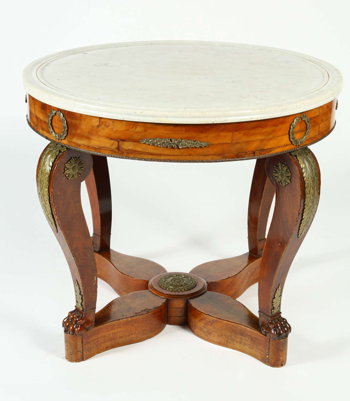 This Gueridon table from the French Restoration Era has a beautiful flame mahogany veneer and a white marble top. Delicate gilt-bronze garniture depicting laurel wreaths, palmettes, and roses decorate the apron, legs, and the star-shaped base. The