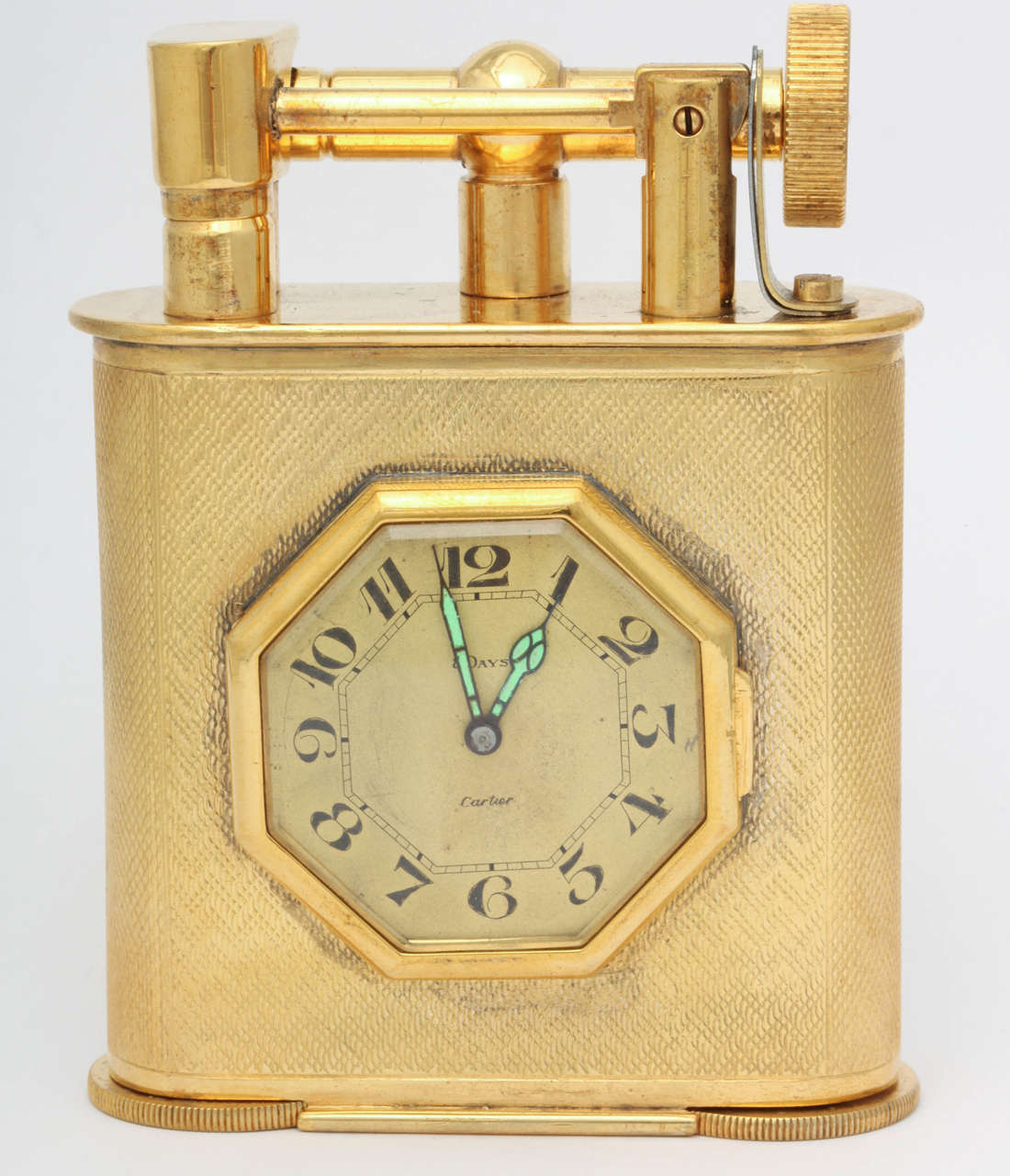 A stunning and exceptionally rare, English made, gold plated table lighter, made for and retailed by Cartier.  The lighter holds an eight day clock set in an octagonal frame in the center of the lighter's body.   The body is fully engine turned and